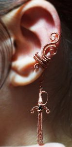 Sword charm on a woven swirly ear cuff